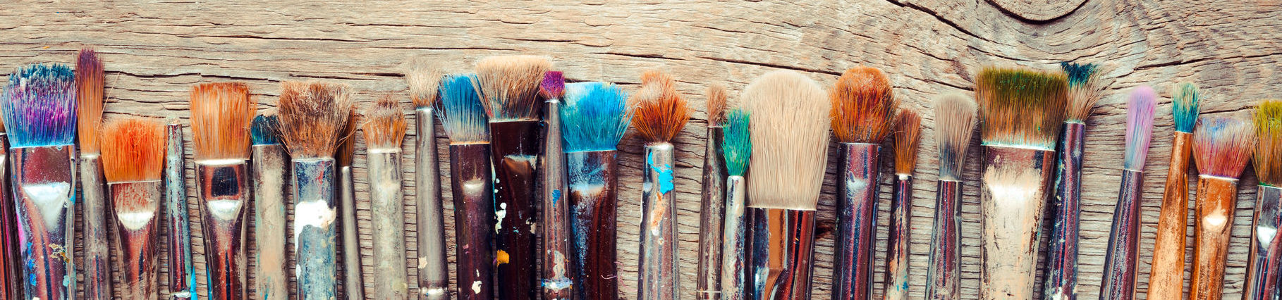 35515339 - row of artist paintbrushes closeup on old wooden rustic background